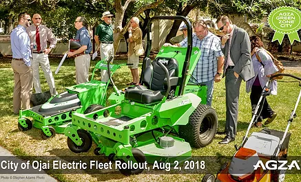 people standing near electric lawn equipment