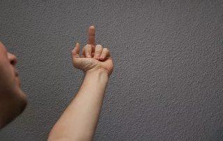 man making obscene hand gesture